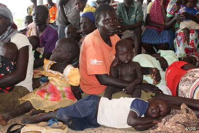 A South Sudanese mother with her children wait in queue at a health center in Maaji settlement, Adjumani district, northern Uganda, June 14, 2017. (H. Athumani/VOA)
