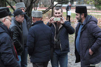 FILE - People, including Crimean Tatars, gather near a court building before the expected arrival of crew members of Ukrainian naval ships, which were recently seized by Russia's FSB security service, in Simferopol, Crimea, Nov. 27, 2018.