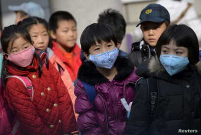 Schoolchildren wear masks as they leave school early at noon due to heavy air pollution, at a primary school in Shenyang, Liaoning province, Nov. 13, 2015.