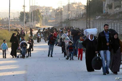 This Nov. 27, 2016 photo provided by the Rumaf, a Syrian Kurdish activist group, shows people fleeing rebel-held eastern neighborhoods of Aleppo into the Sheikh Maqsoud area that is controlled by Kurdish fighters.