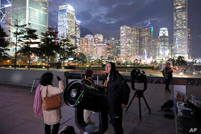 Stargazers use telescopes to observe the moon along the Victoria Habour in Hong Kong, Jan. 31, 2018.