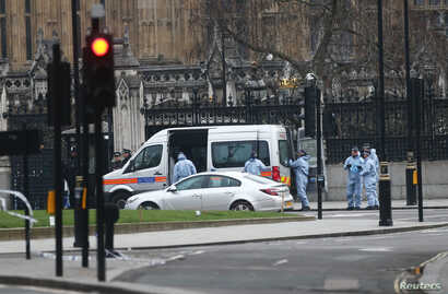 FILE - Police work at Carriage Gate outside the Houses of Parliament the morning after an attack by a man driving a car and weilding a knife left five people dead and dozens injured, in London, Britain, March 23, 2017.