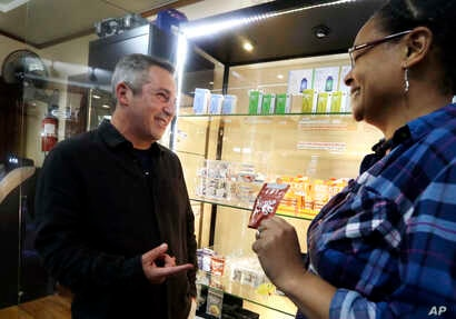 Adam Smith, left, founder and executive director of Oregon Craft Cannabis Alliance, is shown a variety of edible marijuana products by Tree PDX marijuana shop owner Brooke Smith at her shop in Portland, Ore.