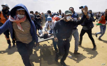 Palestinian medics and protesters evacuate a seriously wounded youth during a deadly protest at the Gaza Strip's border with Israel, east of Khan Younis, Gaza Strip, May 14, 2018.