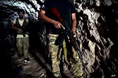 FILE - Fighters with the Free Syrian army leave a cave where they live after rebels and an al-Qaida-linked alliance pulled back their heavy weaponry, in the outskirts of the northern town of Jisr al-Shughur, Syria, west of the city of Idlib, Sept. 9,...