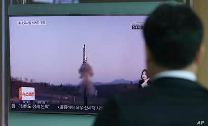 """A man watches a TV report about North Korea's missile firing with file footage, at Seoul Train Station in Seoul, South Korea, April 6, 2017. The letters read """"U.S., North, Scud missile-ER."""""""