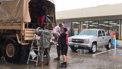 Trestian Woodard, 7, finds welcoming arms at a gas station doubling as a rescue transfer point in north Houston, Texas, Aug. 27, 2017. National Guard and Aldine Fire & Rescue members collected people from the Greenbriar Colony neighborhood. (C. Mendo...