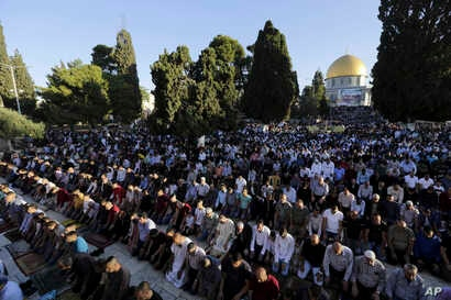 Palestinians pray in front of the Dome of the Rock shrine in Jerusalem, June 15, 2018 during the traditional morning prayer of the Muslim holiday of Eid al-Fitr.