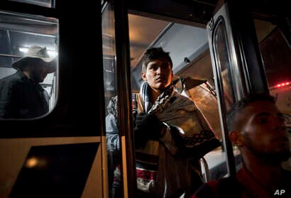 Central American migrants arrive in a bus at a shelter for migrants in Tijuana, Mexico, Nov. 20, 2018.