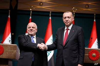 Iraq's Prime Minister Haider al-Abadi, left, shakes hands with Turkey's President Recep Tayyip Erdogan, following a joint news conference after their meeting at the Presidential Palace in Ankara, Turkey, Aug. 14, 2018.