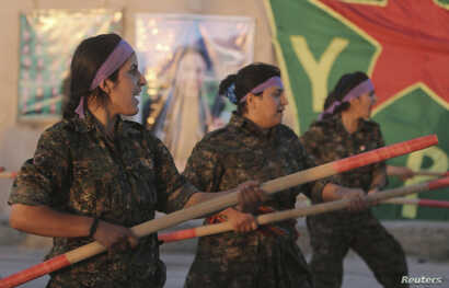 FILE - Kurdish female fighters of the Women's Protection Unit (YPJ) participate in training at a military camp in Ras al-Ain city in Syria's Hasakah province June 30, 2014.