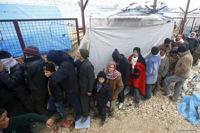 Internally displaced Syrians line up to receive blankets near the Bab al-Salam crossing, across from Turkey's Kilis province, on the outskirts of the northern border town of Azaz, Syria, Feb. 6, 2016.
