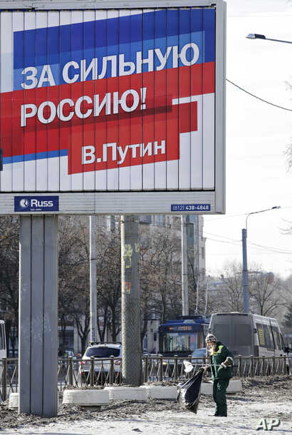 """A municipal worker collects rubbish under an election poster for Russian President Vladimir Putin in St. Petersburg, Russia, March 17, 2018. The sign on poster reads: """"For the strong Russia! Vladimir Putin."""""""