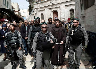 Israeli police forces escort Franciscan priests along the Via Dolorosa (Way of Suffering) in Jerusalem's Old City during the Good Friday procession on March 25, 2016.