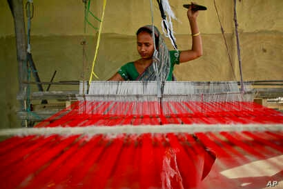 FILE - An Indian woman weaves at Panbari village in northeastern Assam state, India, April 12, 2016.