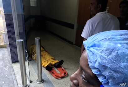 A man lies at the floor in the emergency area of Dr. Miguel Perez Carreno Hospital, in the west of Caracas, Venezuela, Dec. 31, 2018.
