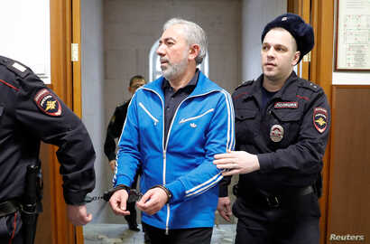 Partner in the Baring Vostok private equity group Vagan Abgaryan, who was detained on suspicion of fraud, is escorted inside a court building in Moscow, Russia, Feb. 15, 2019.