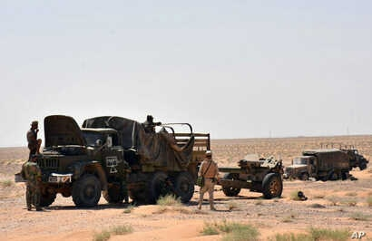 This photo, released Sept. 3, 2017, by the Syrian official news agency SANA, shows Syrian troops and pro-government gunmen standing near military vehicles on the outskirts of the eastern city of Deir el-Zour, Syria.