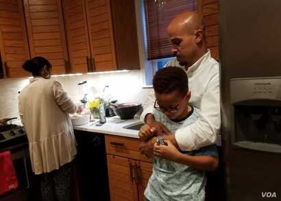 Jeremiah Randall checks his father Jeremy's watch to see how long he must wait for dinner. His stepmother, Ariam Mohamed, prepares a chicken and pasta dish for iftar, a dinner during Ramadan. (C. Guensburg/VOA)
