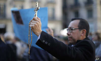 """FILE - A protester holds up a crucifix as protestors gather in front of the city hall during a demonstration organized by a platform in defense of religious freedom, to condemn what they call """"attacks on the rights of believers"""" in Barcelona, Spain."""