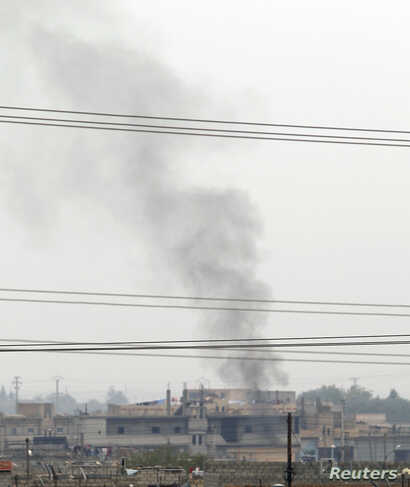Smoke rises over the Syrian town of Ras al-Ain, as seen from the Turkish border town of Ceylanpinar, Sanliurfa province, November 26, 2012.