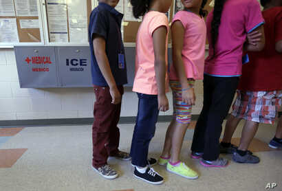 FILE - In this Sept. 10, 2014 file photo, detained immigrant children line up in the cafeteria at the  Karnes County Residential Center,  a temporary home for immigrant women and children detained at the border, in Karnes City, Texas.