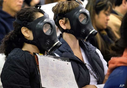 FILE - Protesters wearing gas masks, attend a hearing about a gas leak at the southern California Gas Company's Aliso Canyon Storage Facility near the Porter Ranch section of Los Angeles. The Los Angeles County Department of Public Health released re...