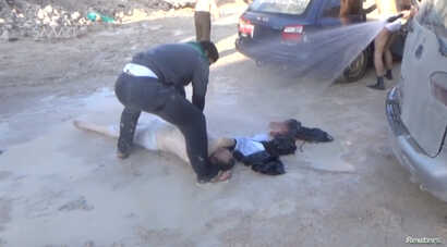 A still image taken from a video posted to a social media website on April 4, 2017, shows a man lying on the ground and being sprayed with water, said to be in the town of Khan Sheikhoun.