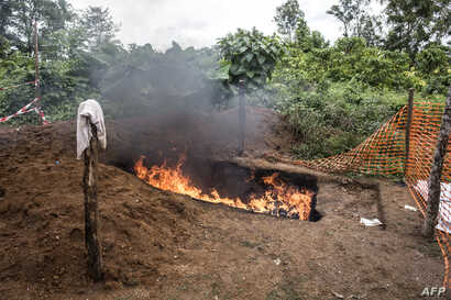 Health workers burn mattresses used by patients with Ebola virus, on Aug. 21, 2018 in Mangina, near Beni, in the North Kivu province of the DRC.