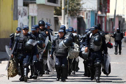 Police officers patrol a street after a blockade set by members of the Santa Rosa de Lima Cartel to repel security forces during an anti-fuel theft operation in Santa Rosa de Lima, in Guanajuato state, Mexico, March 6, 2019.