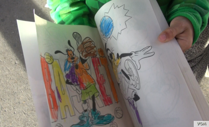 Alex shows his coloring book that someone in Mexico donated to him. The eight-year-old a migrant child from Honduras was waiting at the El Paso del Norte Bridge between Mexico and the U.S. with his father for a chance to request asylum. (VOA video sc...