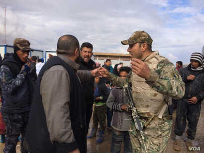 Soldiers explain security procedures intended to catch any militants trying to flee with families as they arrive at camps outside of Mosul on March 19, 2017 in Hammam Aleel, Iraq. (H.Murdock/VOA)