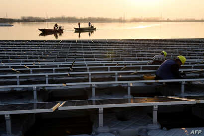 FILE - Chinese employees working, Dec. 11, 2017, on a floating solar power plant in Huainan, a former coal-mining region, in China's eastern Anhui province.