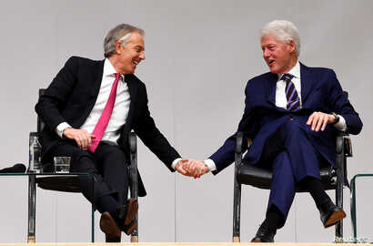 Tony Blair and Bill Clinton hold hands during an event to celebrate the 20th anniversary of the Good Friday Agreement, in Belfast, Northern Ireland, April 10, 2018.