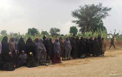 A man carrying a Boko Haram flag walks past a group of 82 Chibok girls, who were held captive for three years by Islamist militants, as the girls wait to be released in exchange for several militant commanders, near Kumshe, Nigeria, May 6, 2017.