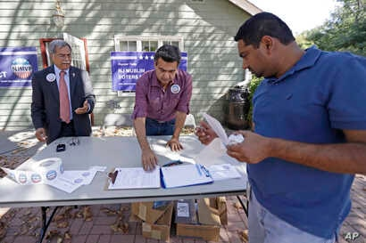In this Sept. 23, 2016, photo, Dr. Mohammad Ali Chaudry, left, president of the Islamic Society of Basking Ridge, New Jersey, and Shawn Butt provide voter registration information to Shahul Feroze, right, after a prayer service.
