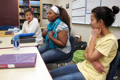 FILE - Nakafu Kahasha, center, describes her short story about her journey from Congo to Tanzania to Fargo, N.D., nearly six years ago, while Nepal natives Anju Tamang, left, and Anju Gurung listen during their English-language learners class at Farg...