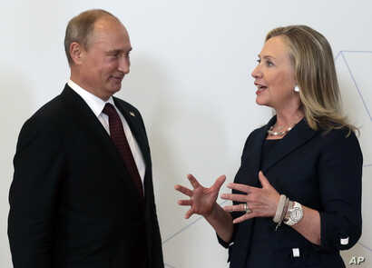 Russian President Vladimir Putin, left, meets U.S. Secretary of State Hillary Rodham Clinton on her arrival at the APEC summit in Vladivostok, Russia, Sept. 8, 2012.