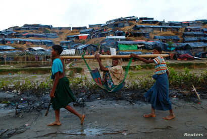 Rohingya refugees carry an old woman in a sling near Balukhali makeshift refugee camp in Cox's Bazar, Bangladesh, Sept. 13, 2017.