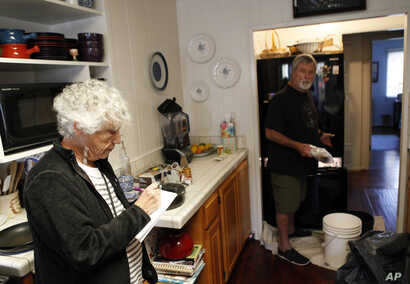 Pamela Arneson writes down the food that was lost as Eric Arneson, 72, cleans out the refrigerator after returning to their home for the first time in almost two weeks in Montecito, Calif., Jan. 25, 2018.