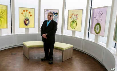 """Glass artist Dale Chihuly poses for a picture in front of his """"Glass on Glass"""" pieces in a reflection room at the Fred & Pamela Buffett Cancer Center in Omaha, Nebraska, May 19, 2017."""