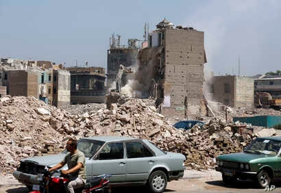 Heavy machinery is used to demolish buildings in the Maspero neighborhood of Cairo, Egypt, July 31, 2018. Egyptian authorities are demolishing the neighborhood to make way for development, angering residents who say they have not been properly compen...
