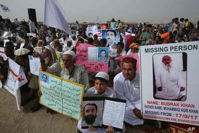 Members and supporters of the Pashtun Protection Movement hold pictures of missing family members during a rally in Karachi, Pakistan, May 13, 2018.
