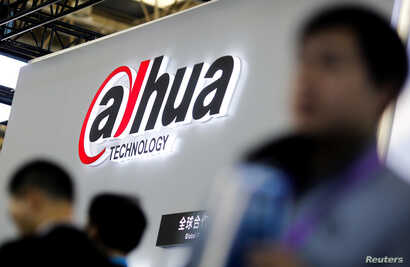 Visitors stand in front of a stall of the video surveillance product maker Dahua Technology at the Security China 2018 exhibition on public safety and security in Beijing, China Oct. 23, 2018.