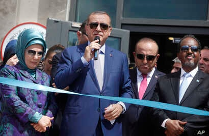 FILE - From left, Turkey's first lady Emine Erdogan, President Recep Tayyip Erdogan, Foreign Minister Mevlut Cavusoglu and Somali President Hassan Sheikh Mohamud at a new Turkish embassy in Mogadishu, Somalia, June 3, 2016.