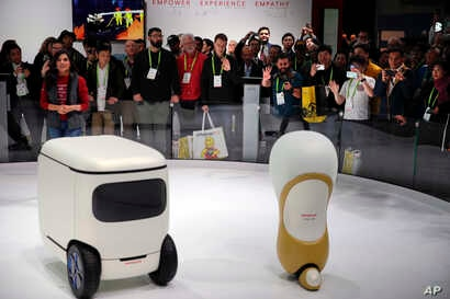 Attendees wave at Honda robotics concepts 3E-C18, left, and 3E-A18, at CES International, in Las Vegas, Nevada, Jan. 9, 2018.