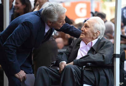 Honoree Michael Douglas, left, speaks with his father Kirk Douglas before a Hollywood Walk of Fame star ceremony, Nov. 6, 2018, in Los Angeles.