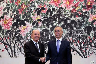 In this June 3, 2018, photo, U.S. Commerce Secretary Wilbur Ross, left, shakes hands with Chinese Vice Premier Liu He as they pose for photographers after their meeting at the Diaoyutai State Guesthouse in Beijing.