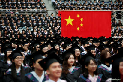 FILE - Students attend a graduation ceremony at Fudan University in Shanghai, June 23, 2017.