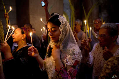 Christians hold candles during the Palm Sunday mass at the Church of the Holy Sepulchre, traditionally believed by many to be the site of the crucifixion and burial of Jesus Christ, in Jerusalem's Old City, Sunday, April 24, 2016.